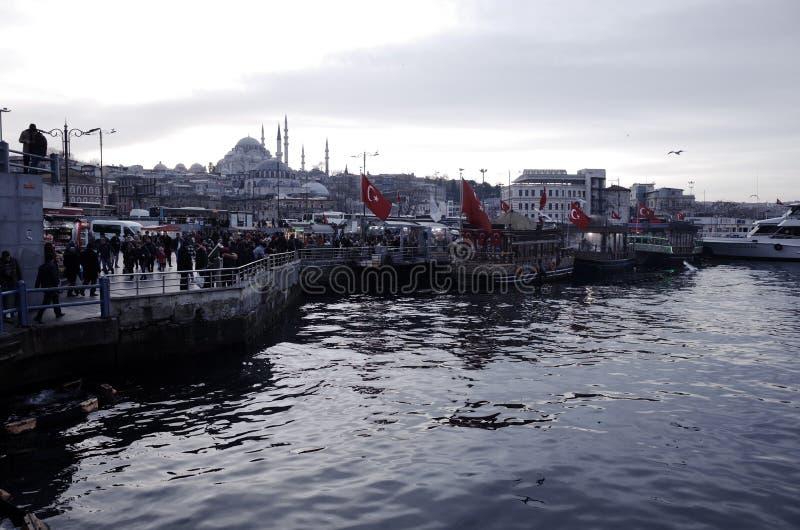 Fish burger boat by Galata Bridge and overlooking Rustam Pasha Mosque stock photo