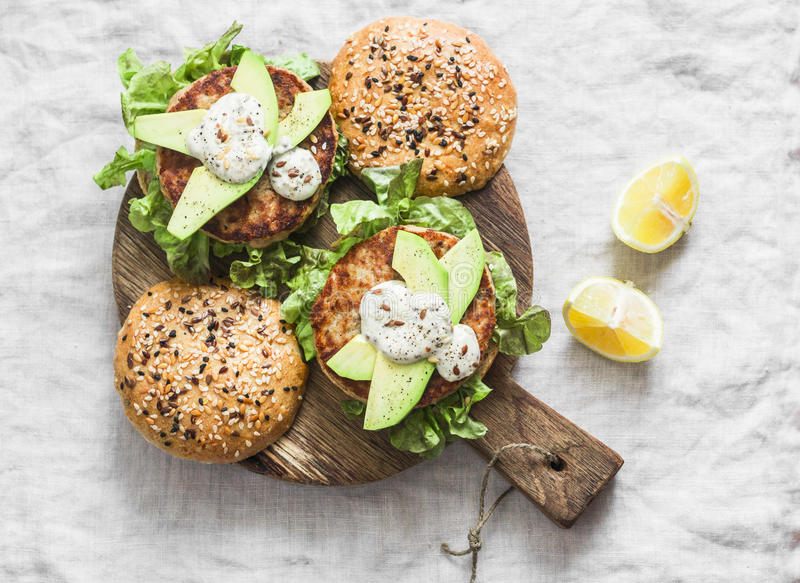 Fish burger. Burgers with tuna, avocado and mustard sauce with whole grain homemade buns on wooden cutting board on a light backgr royalty free stock photo