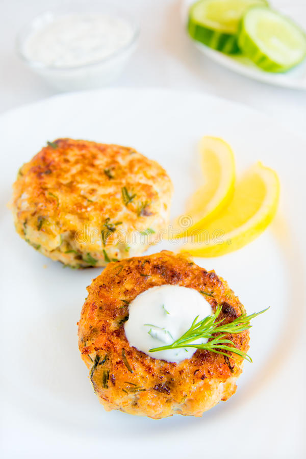Fish cakes (cutlets). Homemade thai fish cakes (cutlets) with white sauce, dill and lemon on plate stock photo