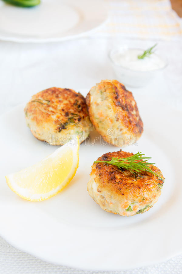 Fish cakes. Homemade fish cakes with dill and lemon on white plate stock photo