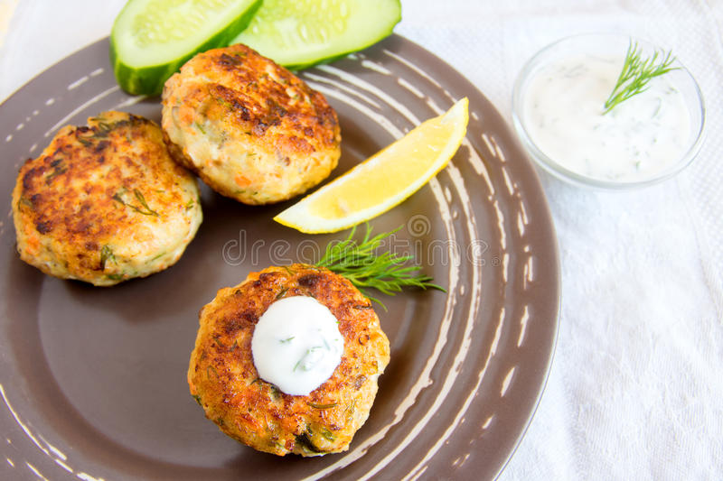 Fish cakes. Homemade thai fish cakes with white sauce, dill and lemon on plate royalty free stock photos