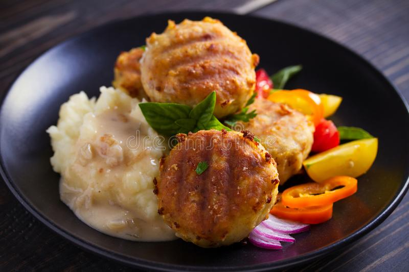 Fish cakes with mashed potatoes and vegetables, garnished with basil. Fish burgers on black table. Horizontal image stock photo