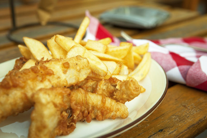 Fish and chips. Traditional british snack on the wooden table royalty free stock image