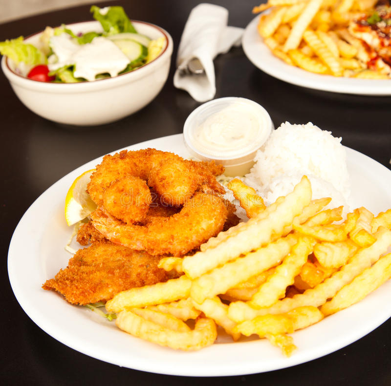 Fish and chips. On a withe plate in a restaurant setting royalty free stock images