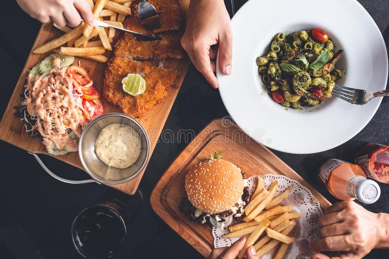 Fish and Chips, Fries and Burger, Pasta Dish on Restaurant Table. On dark Background stock image
