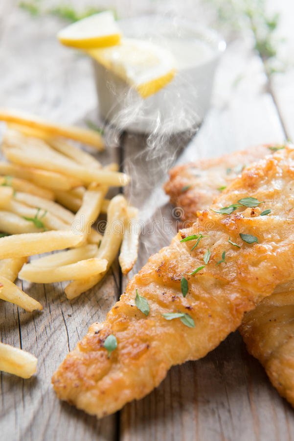 Fish and chips with hot steams. Fish and chips. Fried fish fillet with french fries on wooden background. Fresh cooked with hot steams stock photography