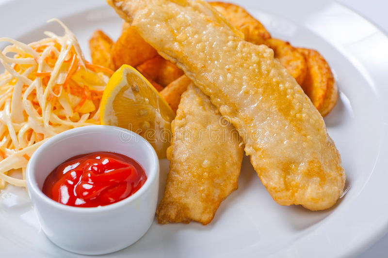 Fish and chips with salad and sauce stock images
