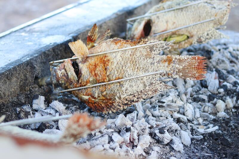 Fish coated with salt grill on the fire. royalty free stock photo