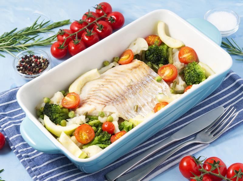 Fish cod baked in blue oven with vegetables - broccoli, tomatoes. Healthy diet food. Blue stone background, side view. royalty free stock photos