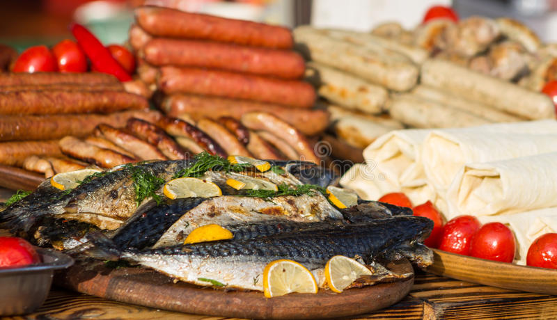 Fish cooked with lemon. Cooked fried fish with lemon, sausages and tomatoes on the table food photo on plate in restaurant royalty free stock images