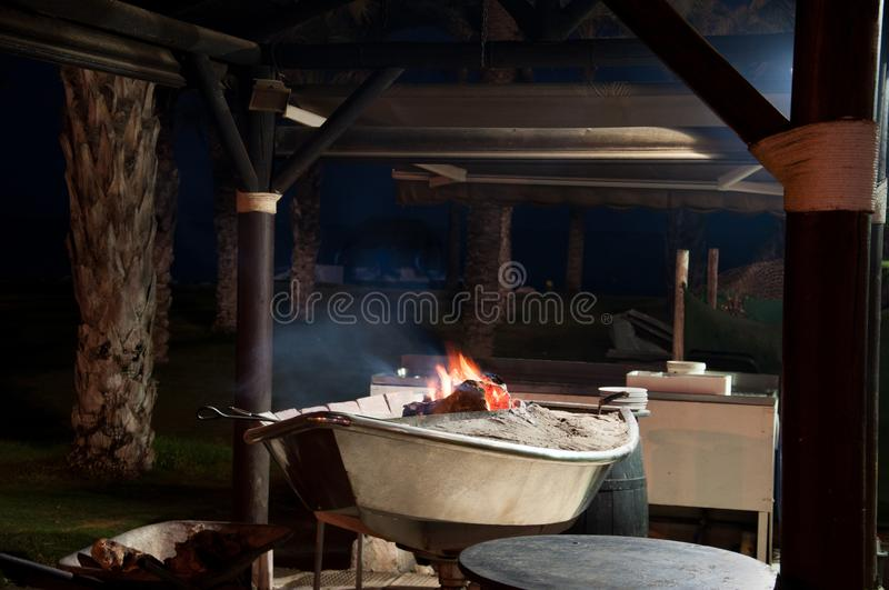 Fish cooking on open beach fire royalty free stock images