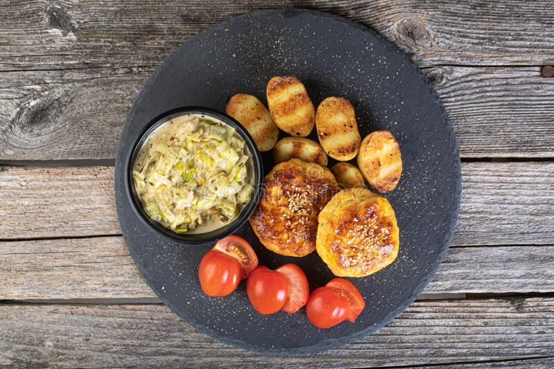 Fish cutlet on a black stone plate. Lunch of fish cutlet with baby potatoes and leek sauce served on a black stone plate royalty free stock images