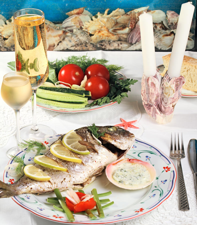 Fish dinner. White vine for the baked gilt-head bream stock image
