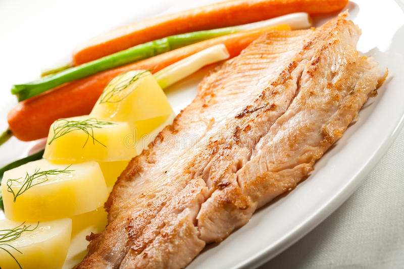 Fish dish. Fried fish fillet with potatoes and vegetables stock photos