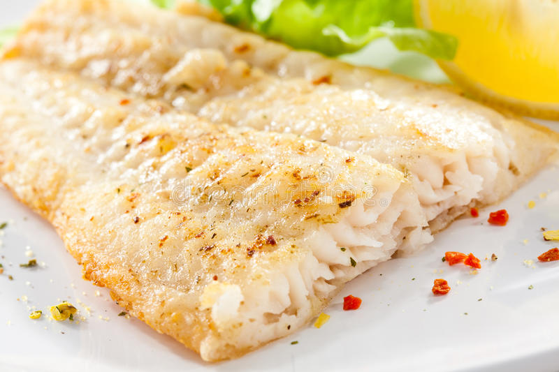 Fish dish. Fried fish fillet with vegetables royalty free stock photos