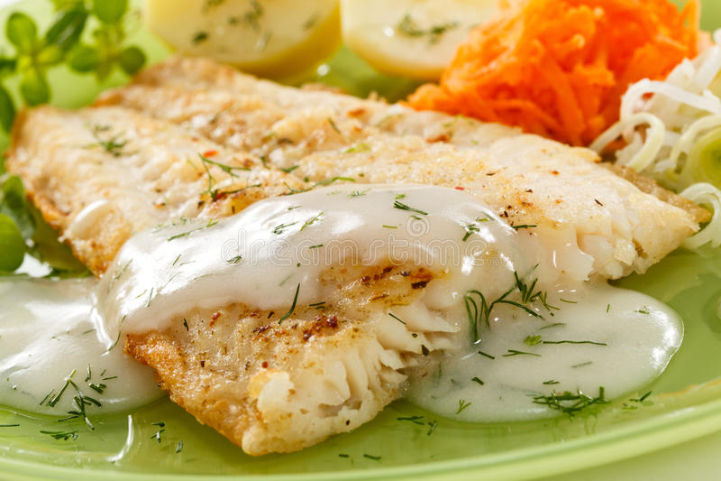 Fish dish. Fried fish fillet with vegetables stock photography