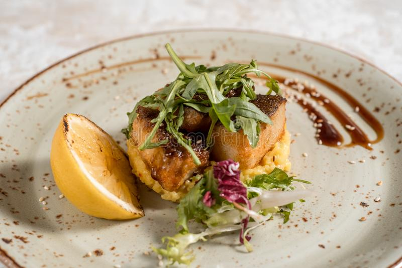 Fish dish - fried fish fillet with fried potatoes and vegetables. Fish dish - fried fish fillet with fried potatoes and lemon. Restaurant menu stock photos
