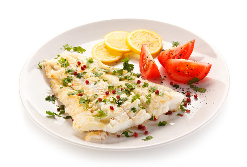Fish dish - fried fish fillet and vegetables. On white background royalty free stock image