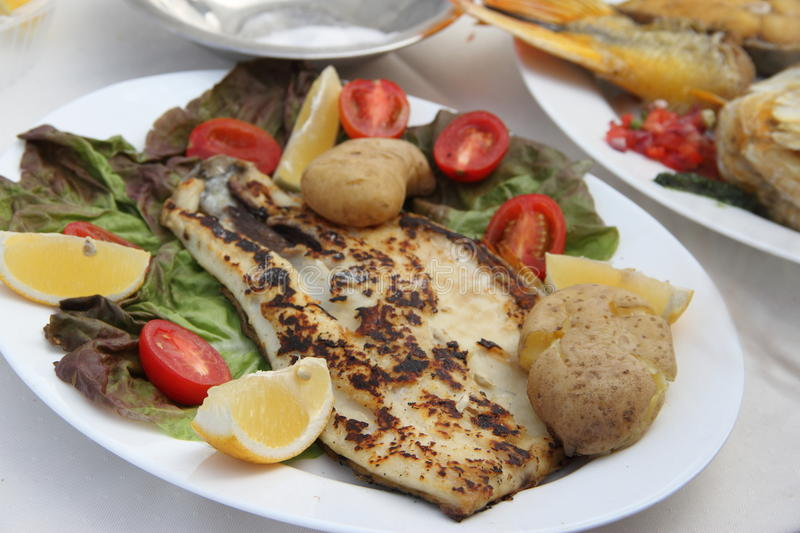 Fish dish. Roasted river  with potatoes and vegetables royalty free stock photos