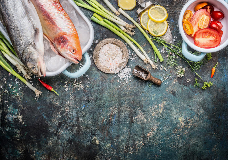 Fish dishes cooking preparation with Raw whole trout fish and Gold Rainbow trout and ingredients on dark rustic background, top vi. Ew, border. Healthy or diet royalty free stock photo