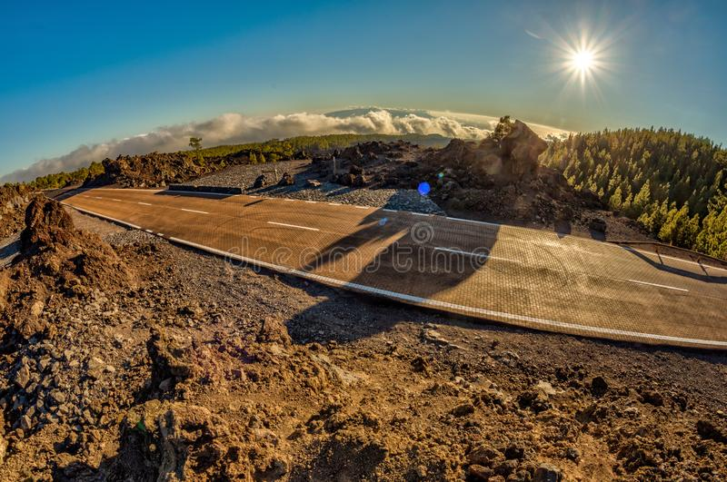 Fish eye lens shot of Sunset time above the clouds in the mountains. Fresh lava fields. Park road crossed pine forest hills. View. Of La Gomera Island royalty free stock image