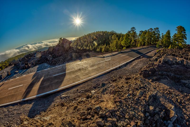 Fish eye lens shot of Sunset time above the clouds in the mountains. Fresh lava fields. Park road crossed pine forest hills. View. Of La Gomera Island stock photo