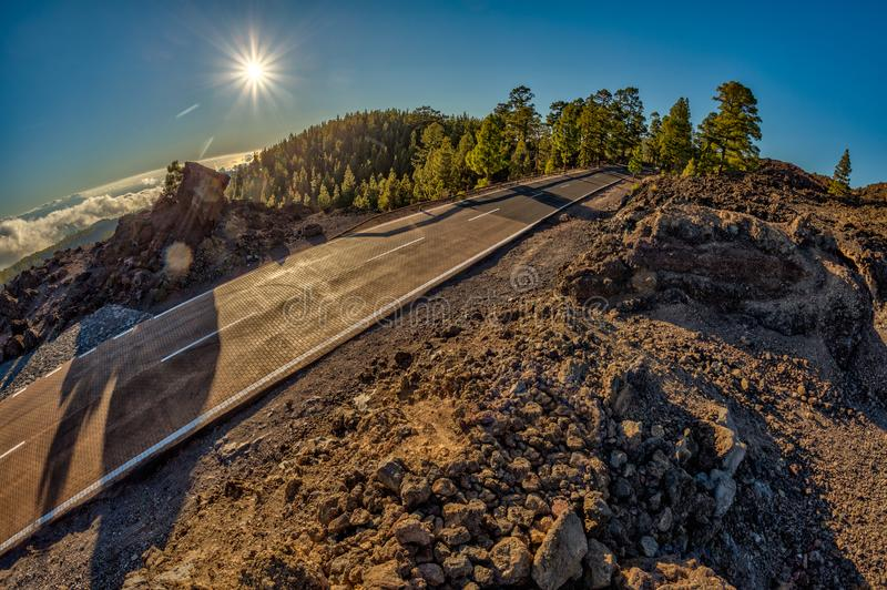 Fish eye lens shot of Sunset time above the clouds in the mountains. Fresh lava fields. Park road crossed pine forest hills. View. Of La Gomera Island royalty free stock photos