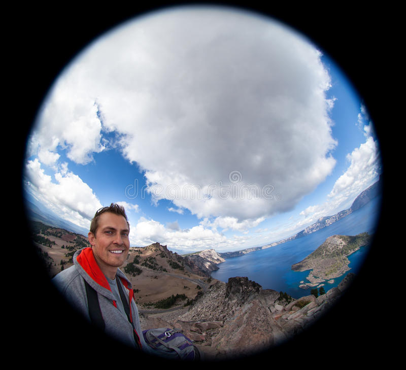 Fish-Eye Selfie at Crater Lake. A dramatic effect selfie of a smiling young man at Crater Lake, Oregon taken with a fish-eye lens royalty free stock photo