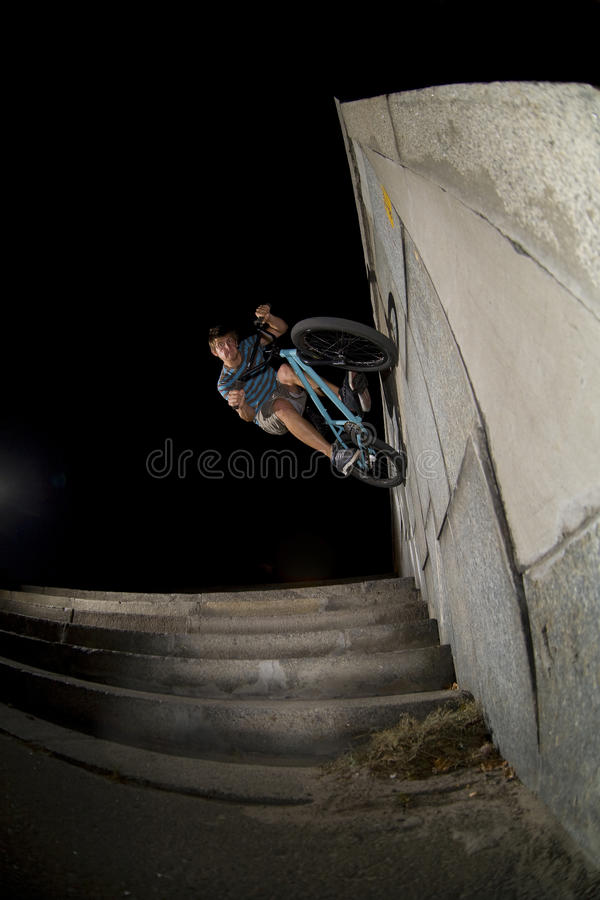 Fish-eye wallride. BMX rider performing a trick wall ride against a black background at night stock image