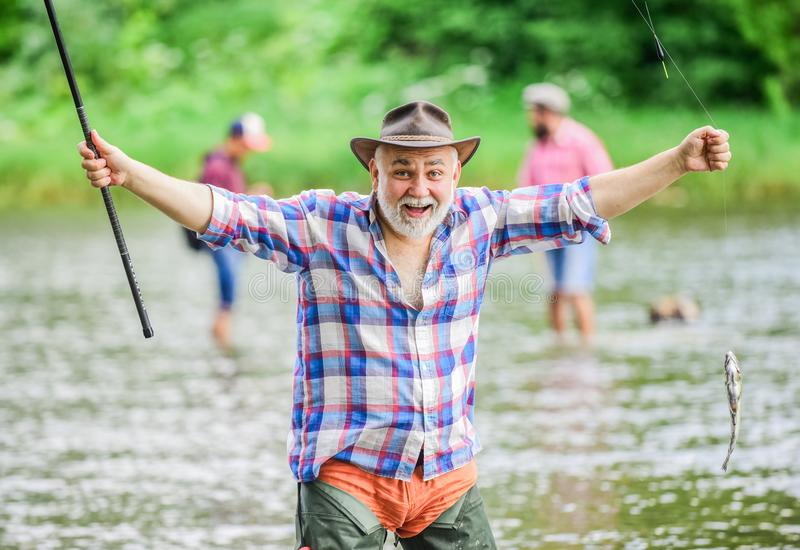 Fish farming pisciculture raising fish commercially. Pensioner leisure. Fish on hook. Man senior fisherman. Fisherman. Fishing equipment. Fisherman alone stand royalty free stock photos