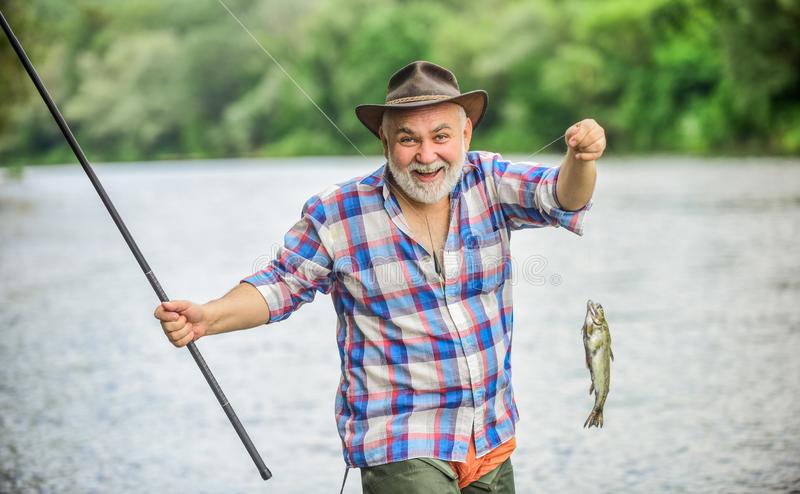 Fish farming pisciculture raising fish commercially. Pensioner leisure. Fisherman alone stand in river water. Hobby. Sport activity. Fish on hook. Man senior royalty free stock photos
