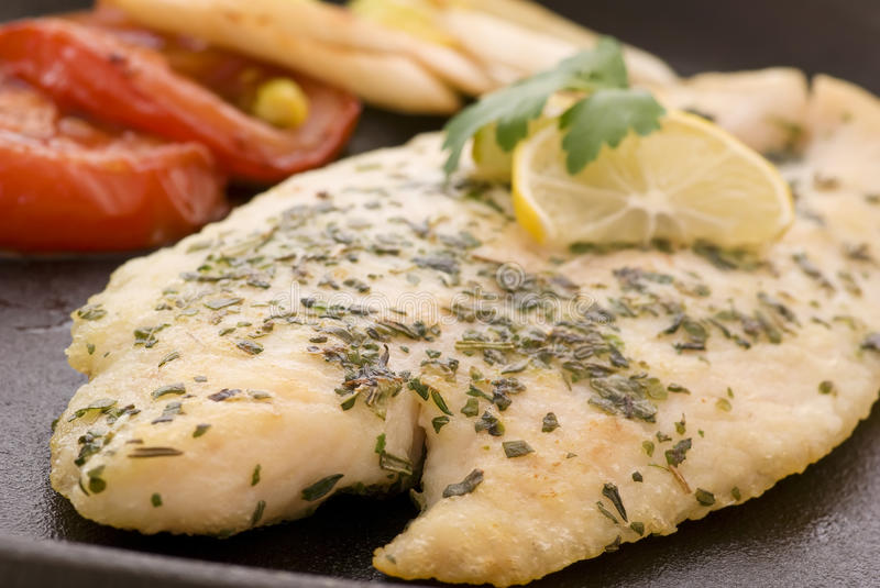 Fish fillet. Catfish fillet with vegetable as closeup in pan royalty free stock photo