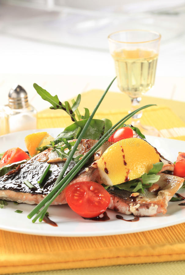 Fish fillet with salad greens and tomatoes royalty free stock photography