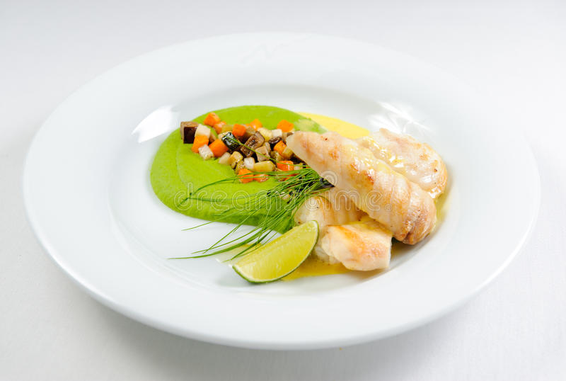 Fish fillet with sauce and vegetables stock image