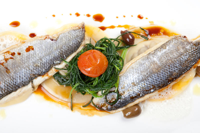 Fish fillet of sea bass. With pasta, olives, spinach and tomato stock images