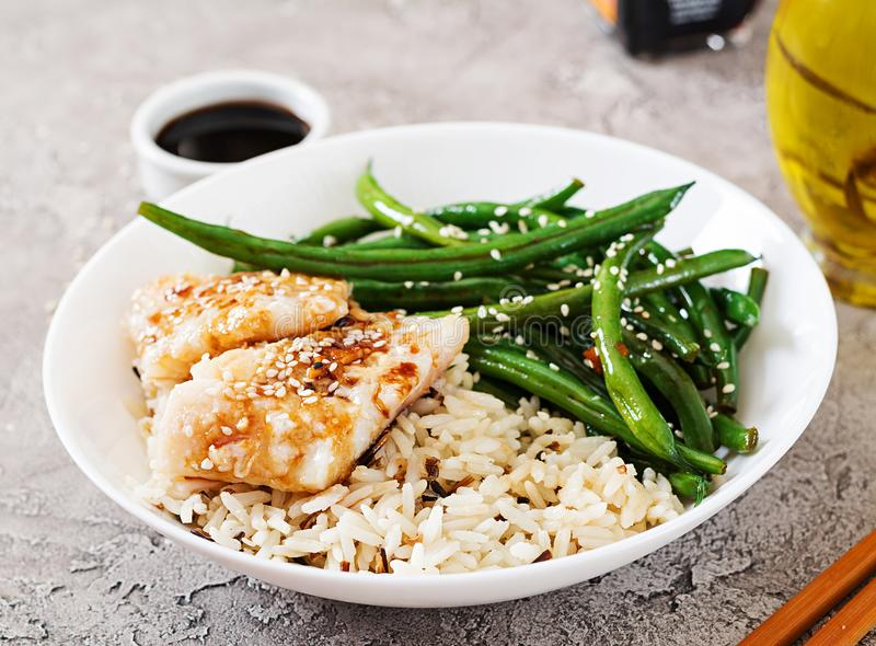 Fish fillet served with rice, soy sauce and green beans in white plate. royalty free stock photo