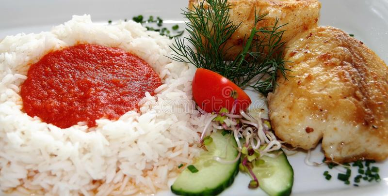 Fish dish with rice and tomato sauce stock photo