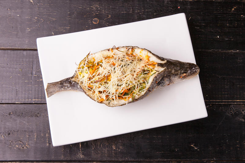 Fish with filling, stuffed with vegetables and cheese on white plate. Top view stock photo