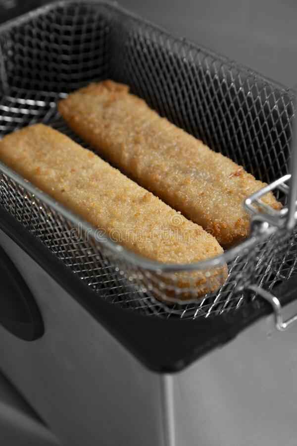 Fish fingers in a mesh basket,  cooked in an electric deep fat fryer appliance. stock image