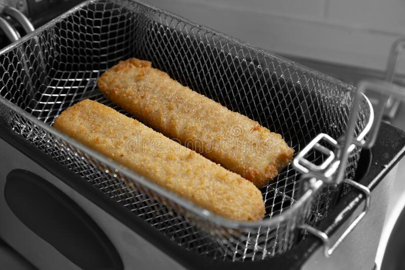 Fish fingers in a mesh basket,  cooked in an electric deep fat fryer appliance. royalty free stock photography