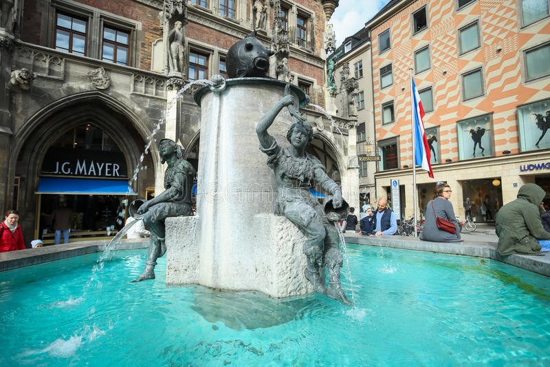 Fish Fountain at Marienplatz. MUNICH, GERMANY - MAY 9, 2017 : People sitting on the edge of Fish Fountain with New Town Hall in the background at Marienplatz in stock photo