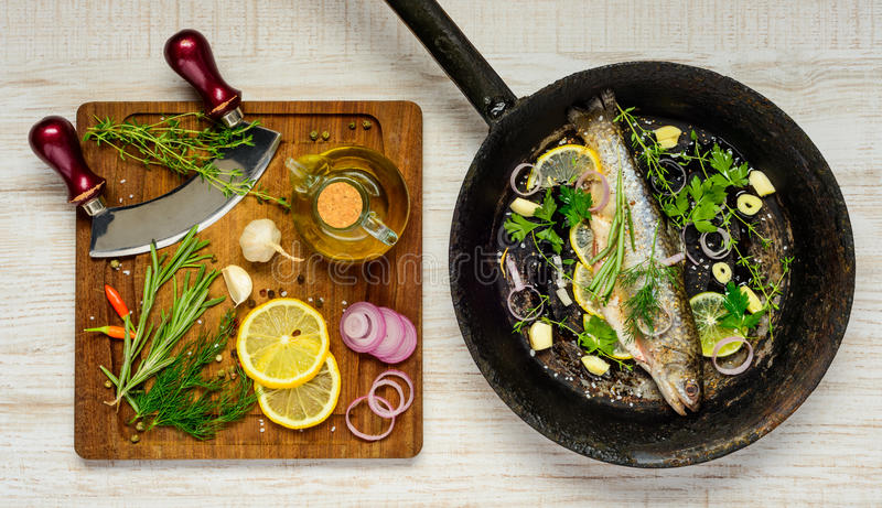 Fish in Frying Pan and Cooking Ingredients stock photography