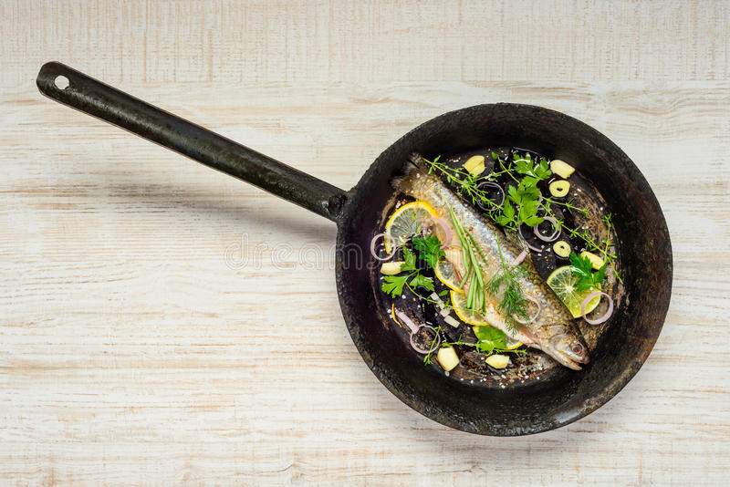 Fish in Frying Pan. Rainbow Trout Fish in Frying pan with spices and Cooking Herbs stock photo