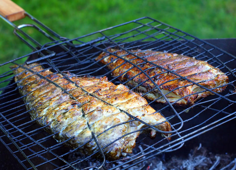 Fish on the grill. Summer barbecue concept. Close up with shallow DOF royalty free stock images