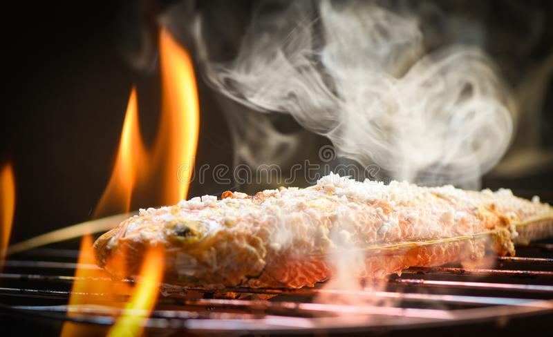 Fish on grill / Close up of seafood grilled fish food with salt on the grill fire and smoke. On dark background stock photo