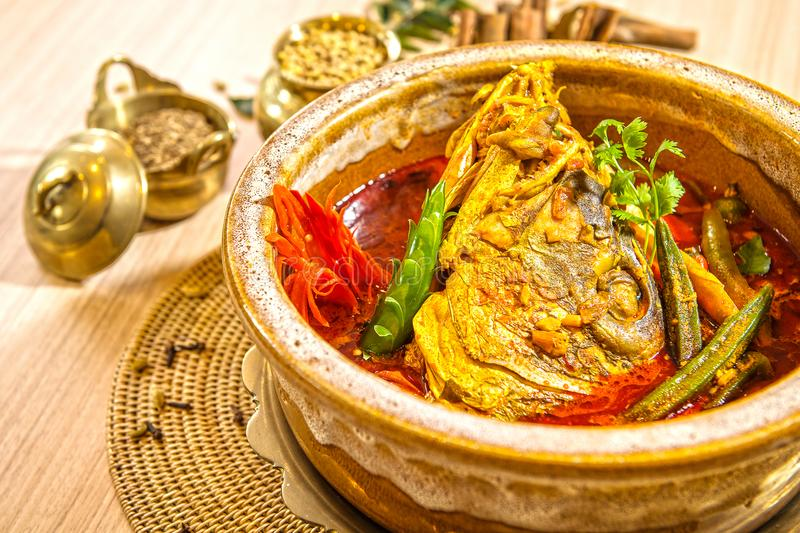 FISH HEAD CURRY. Is a dish in Singaporean and Malaysian cuisine with Indian and Chinese origins. The head of a red snapper is semy-stewed in a Kerala-style stock photography