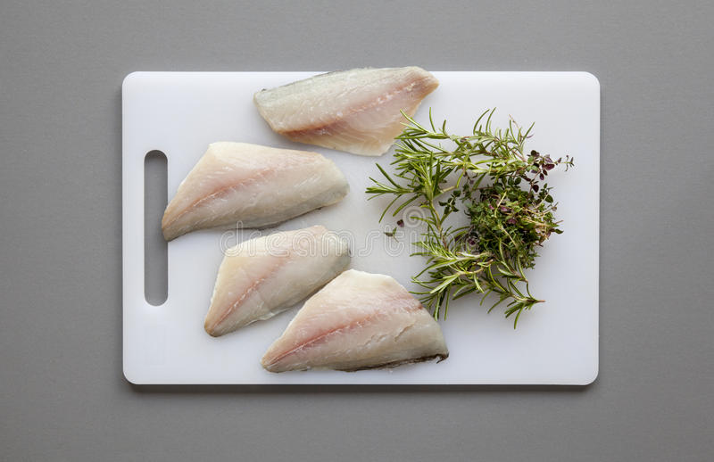 Fish with herbs on the chopping board royalty free stock images