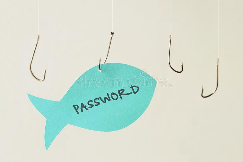 Fish hooks and password written on a paper note in the shape of. A fish - Phishing and internet security concept royalty free stock photography