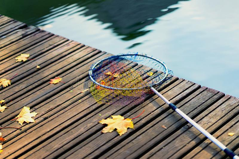 Fish landing net for fish, fishing tackle on a wooden bridge with fallen autumn yellow maple leaves. Minimalistic autumn stock photo