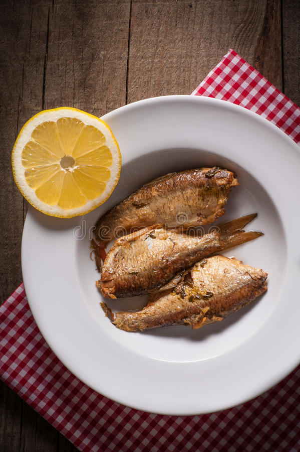 Fish with lemon lobule on plate. Above view of Fish with lemon lobule on white plate on wooden background stock image